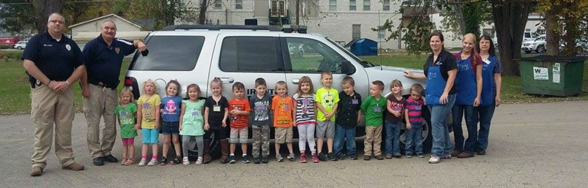 group of children, staff, and law enforcement officers in front of a police vehicle