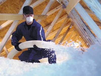 worker blowing insulation in an attic